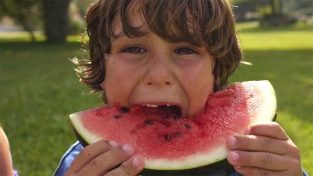 Slow motion close up of boy eating watermelon/Marbella region, Spain