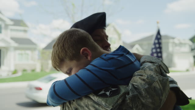 slow motion close up of boy hugging soldier father / lehi, utah, united states - lehi stock videos & royalty-free footage