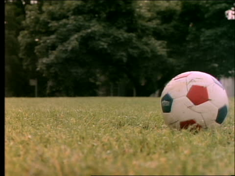 slow motion close up of boy's legs kicking soccer ball on wet grass