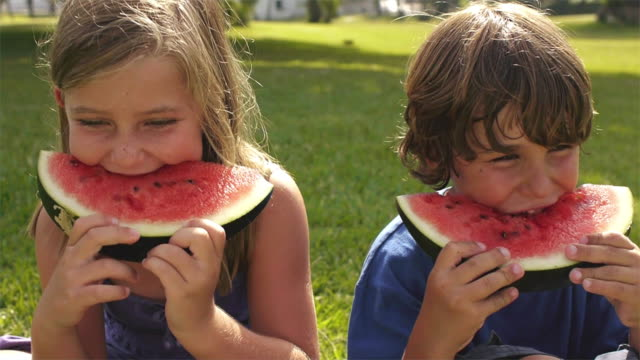 stockvideo's en b-roll-footage met slow motion close up of brother and sister eating watermelon/marbella region, spain - supersensorisch