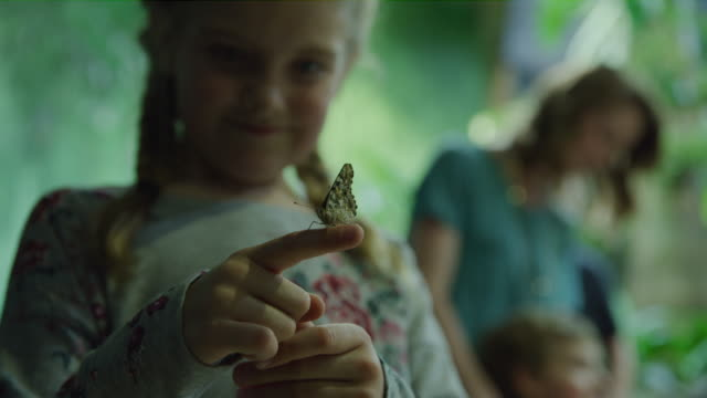 Slow motion close up of butterfly on finger of smiling girl near mother and brother / Draper, Utah, United States