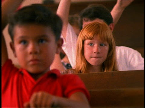 slow motion close up of children raising hands in class - menschlicher arm stock-videos und b-roll-filmmaterial