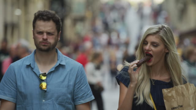 vídeos de stock e filmes b-roll de slow motion close up of couple eating chocolate churro in busy street / barcelona, barcelona, spain - lanche