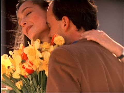 slow motion close up of couple with flowers hugging + kissing - paar mittleren alters stock-videos und b-roll-filmmaterial