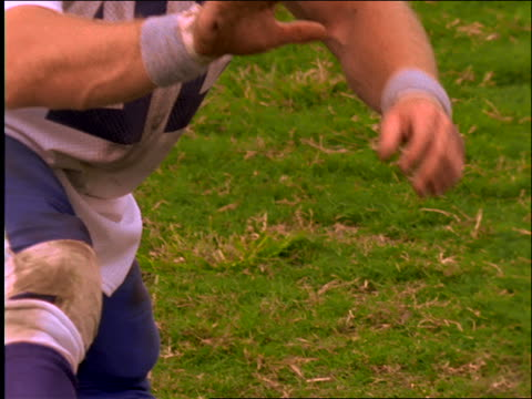 slow motion close up of football being kicked from player's finger