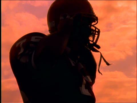 slow motion close up of football player putting on helmet / walks - アメリカンフットボールヘルメット点の映像素材/bロール