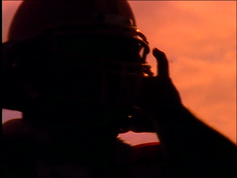 slow motion close up of football player putting on helmet / walks