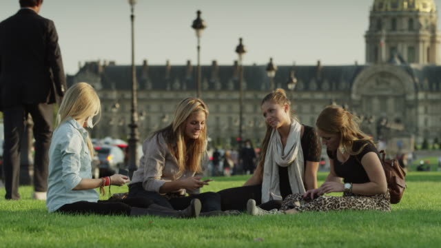 Slow motion close up of friends sitting on grass together / Paris, France