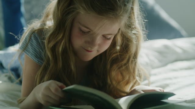 vidéos et rushes de slow motion close up of girl laying on bed and reading book / pleasant grove, utah, united states - tenir