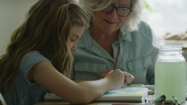 slow motion close up of grandmother watching granddaughter painting with watercolors / pleasant grove, utah, united states - 手提 個影片檔及 b 捲影像