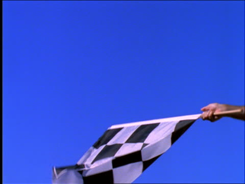 slow motion close up of hand waving checkered flag / car racing - sheppard132 stock videos & royalty-free footage