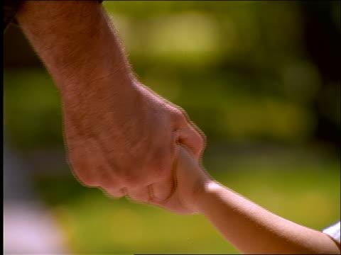 vidéos et rushes de slow motion close up of man and boy holding hands and walking away - se tenir par la main