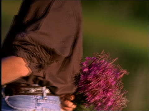 stockvideo's en b-roll-footage met slow motion close up of man giving flowers to woman / kisses her - romance