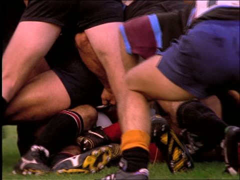 slow motion close up of man grabbing rugby ball from pile of men
