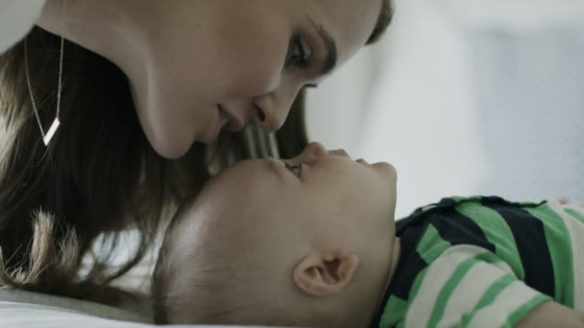 slow motion close up of mother kissing baby son on forehead / american fork, utah, united states - forehead stock videos & royalty-free footage