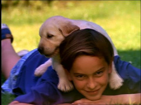 slow motion close up of puppy lying on boy's back in grass