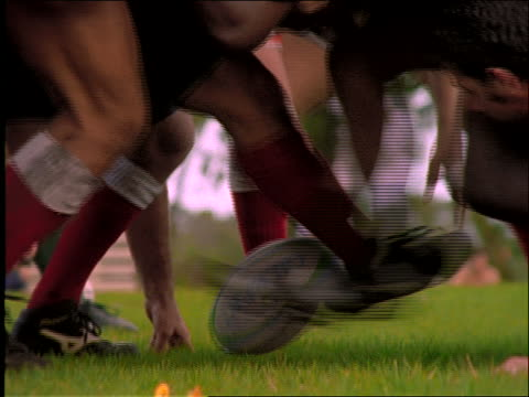 slow motion close up of rugby players' legs kicking ball in match
