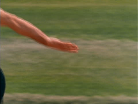 slow motion close up of runner passing baton to other in relay race