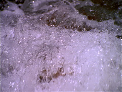 vídeos de stock, filmes e b-roll de slow motion close up of water in small waterfall in stream - stream flowing water