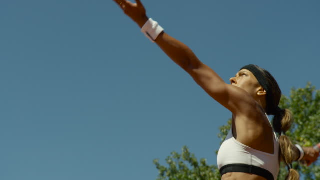 slow motion close up of woman serving tennis ball against blue sky - serving sport stock videos and b-roll footage