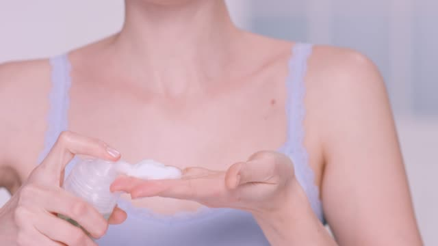 slow motion close up of woman squirting foam cleanser into her hand. - foam hand stock videos and b-roll footage