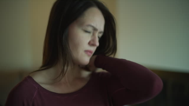 slow motion close up of woman suffering from headache and neck pain / murray, utah, united states - neck stock videos & royalty-free footage
