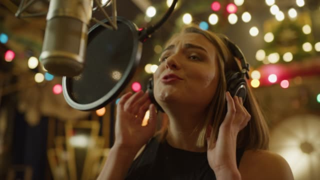 slow motion close up of woman wearing headphones recording vocals with microphone / provo, utah, united states - provo stock videos & royalty-free footage