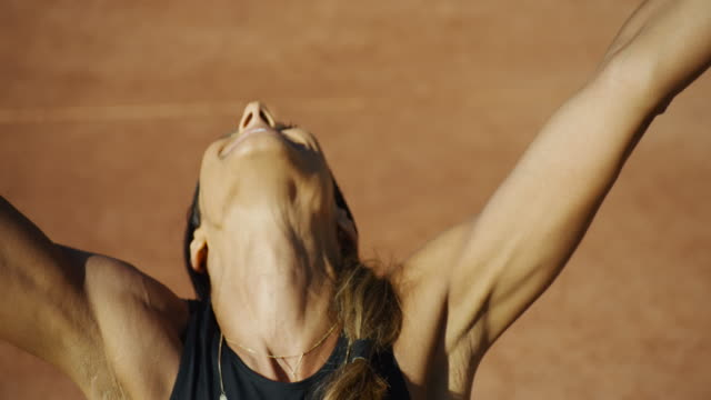 slow motion close up of woman's neck and head as she celebrates on clay tennis court - successo video stock e b–roll