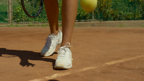 slow motion close up of woman's white sneakers and camera pan up as she prepares to serve - sports court stock videos & royalty-free footage