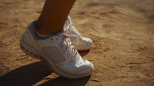 vídeos de stock e filmes b-roll de slow motion close up of woman's white tennis shoes, pivoting and shuffling on clay tennis court - ténis calçado desportivo