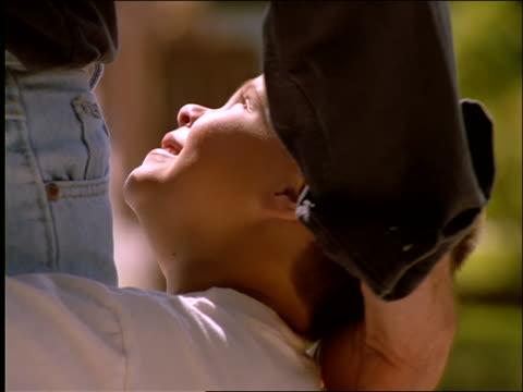 stockvideo's en b-roll-footage met slow motion close up of young boy hugging man's legs - mid volwassen mannen