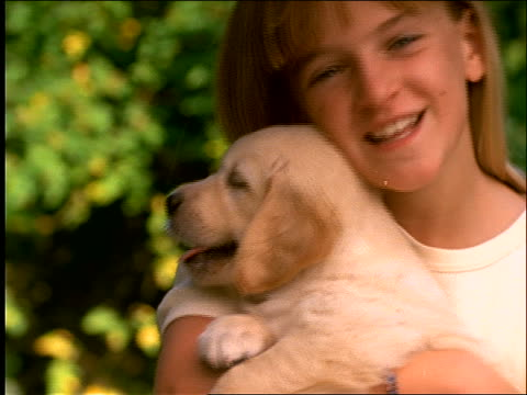 slow motion close up of young girl holding puppy and smiling
