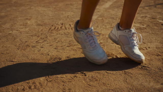 vídeos de stock e filmes b-roll de slow motion close up of young woman's white tennis shoes on clay court - ténis calçado desportivo