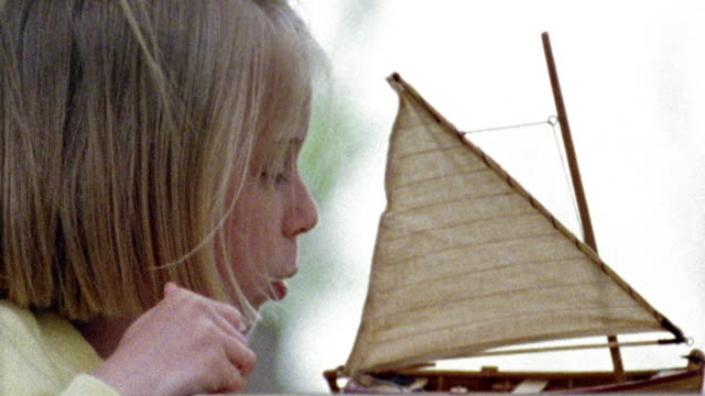 vídeos de stock e filmes b-roll de slow motion close up pan young blonde girl blowing on sail of toy boat in birdbath / missouri - soprar