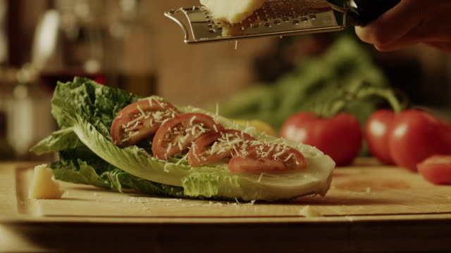 slow motion close up panning shot of cheese being grated over lettuce and tomato / cedar hills, utah, united states - grated stock videos & royalty-free footage