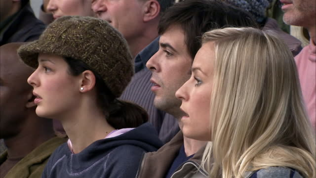 Slow motion close up people at sporting event standing up and clapping/ England