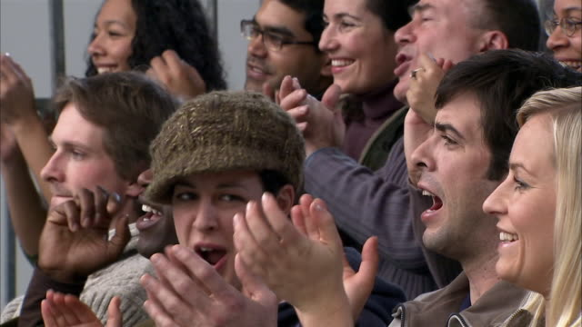 Slow motion close up people clapping at sporting event/ England
