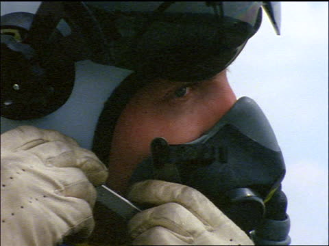 slow motion close up pilot in helmet attaching oxygen mask to face + closing visor - oxygen mask stock videos and b-roll footage
