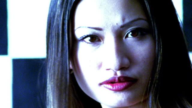 vídeos de stock, filmes e b-roll de blue high contrast slow motion close up portrait asian woman turning to camera - superexposto
