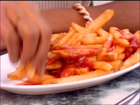 slow motion close up PORTRAIT Black woman putting ketchup on french fries + eating them outdoors