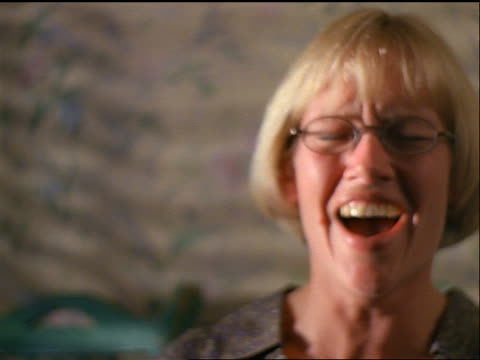 slow motion close up PORTRAIT blonde woman with eyeglasses looking surprised + laughing uncontrollably indoors