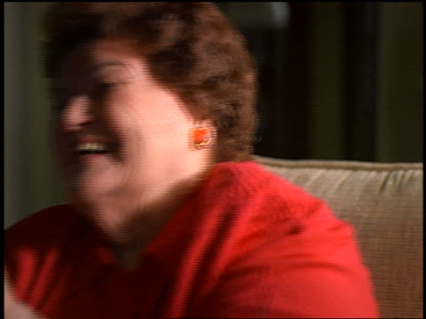 vídeos de stock, filmes e b-roll de slow motion close up portrait heavy middle-aged woman sitting in chair laughing + covering face with hands - só uma mulher madura