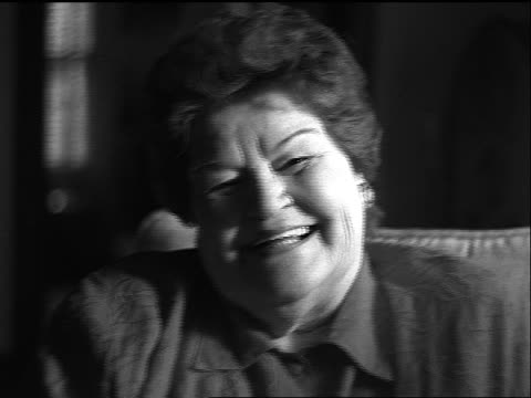 vídeos de stock, filmes e b-roll de b/w slow motion close up portrait heavy middle-aged woman sitting in chair indoors laughing - idade humana