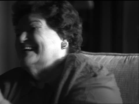 vídeos de stock, filmes e b-roll de b/w slow motion close up portrait heavy middle-aged woman sitting in chair laughing + covering face with hands - mãos cobrindo boca