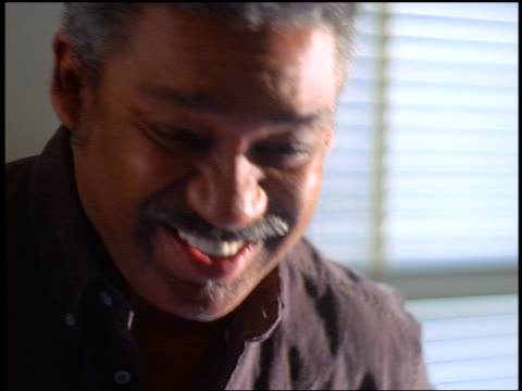slow motion close up portrait middle-aged black man with grey hair + mustache laughing indoors - einzelner mann über 40 stock-videos und b-roll-filmmaterial