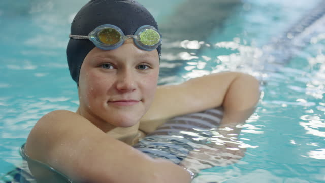slow motion close up portrait of serious girl floating in swimming pool / provo, utah, united states - provo video stock e b–roll
