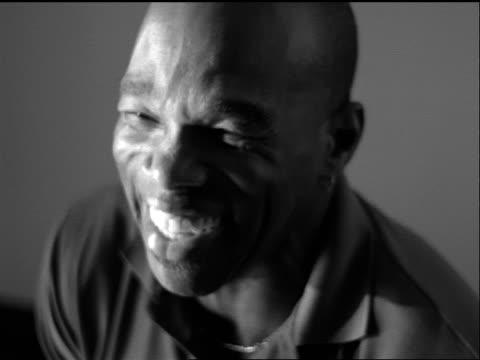 vidéos et rushes de b/w slow motion close up portrait seated black bald man laughing indoors - calvitie