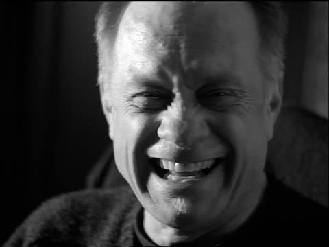 b/w slow motion close up portrait seated middle-aged man laughing indoors - only mature men stock videos & royalty-free footage