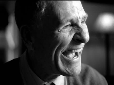 vídeos y material grabado en eventos de stock de b/w slow motion close up portrait seated senior man laughing uncontrollably indoors - blanco y negro