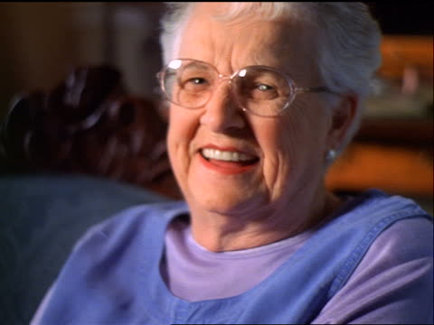 slow motion close up PORTRAIT seated senior woman with eyeglasses laughing indoors